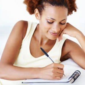 woman writing a to-do list in a notebook