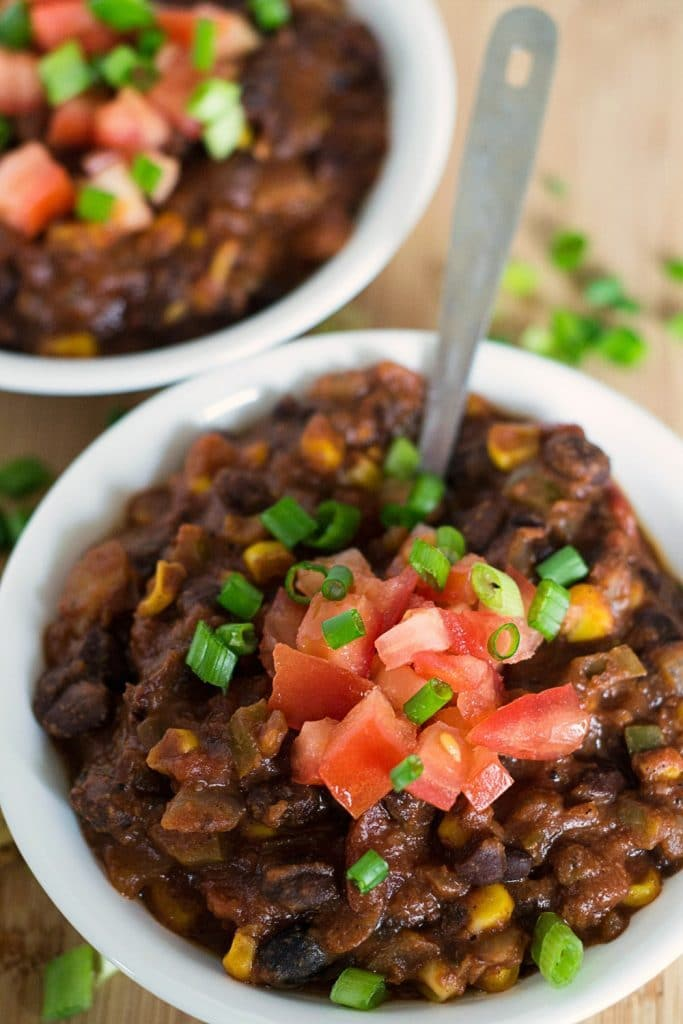 vegan black bean and corn chili in white bowls