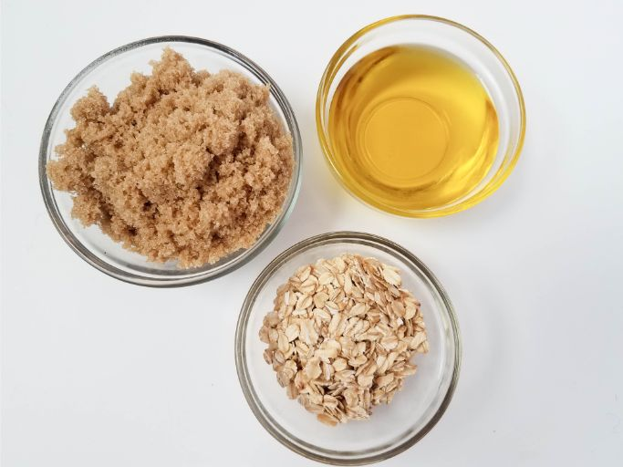 three small glass bowls containing brown sugar, olive oil, and oatmeal
