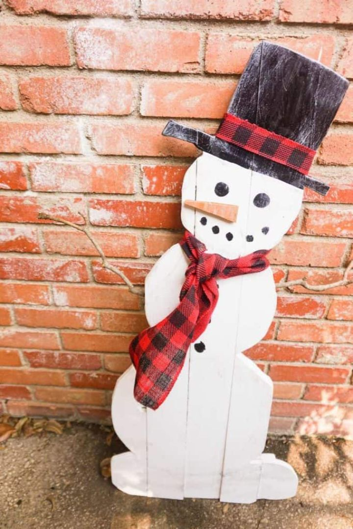 wooden snowman against a brick background