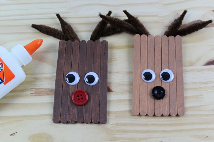 googly eyes and buttons glued to the face of the reindeer ornaments
