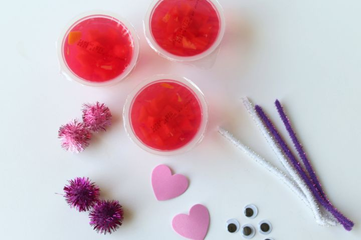 pipe cleaners, pom poms, foam hearts, fruit cups on a white background