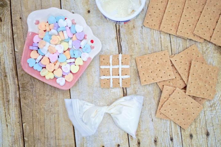 creating a tic tac toe board on the graham crackers using white icing