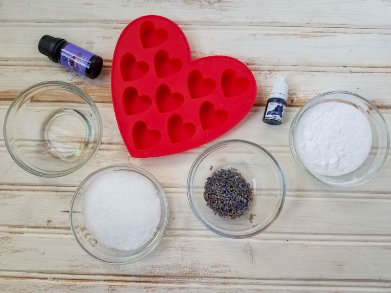 materials for the lavender shower melts - heart mold, lavender essential oil, baking soda, epsom salts, and soap colorant