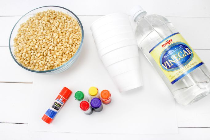 materials for corn mosaic including paper, popcorn kernels, glue, food coloring, white vinegar, and cups
