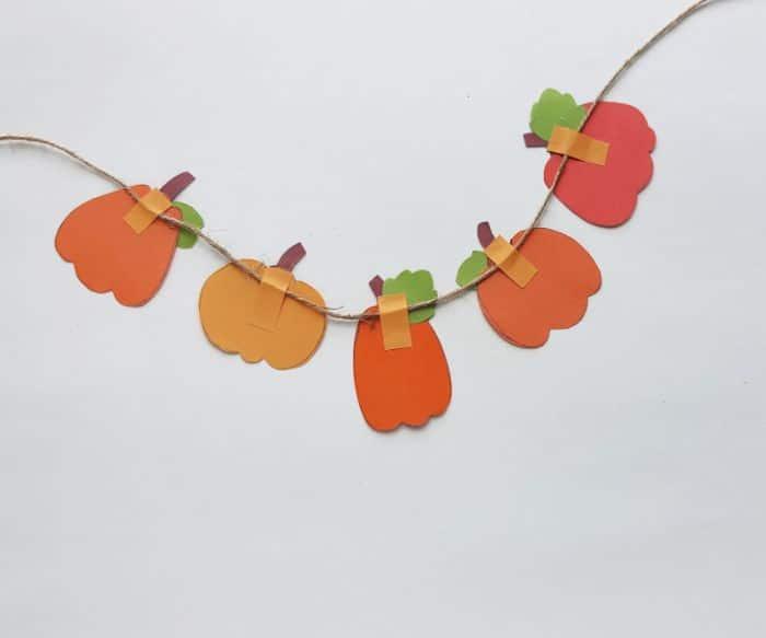adding pumpkins to the garland