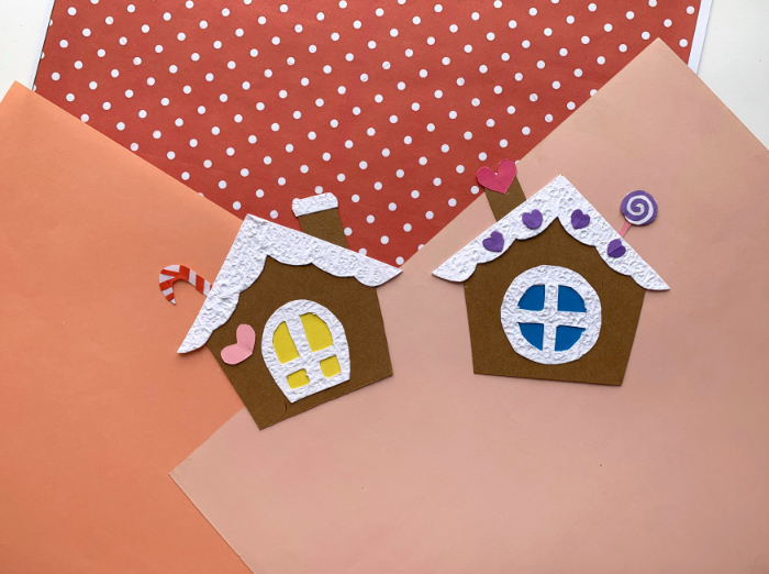 two paper gingerbread houses on pink scrapbook paper