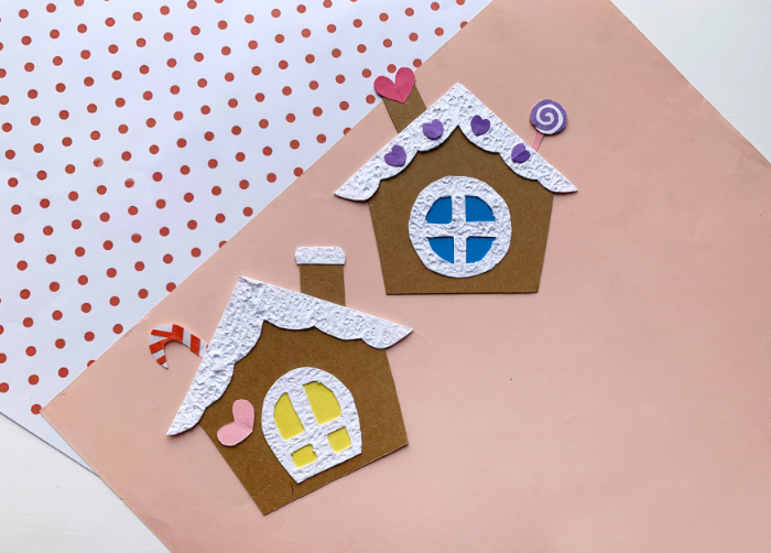 picture of paper gingerbread houses on light pink background
