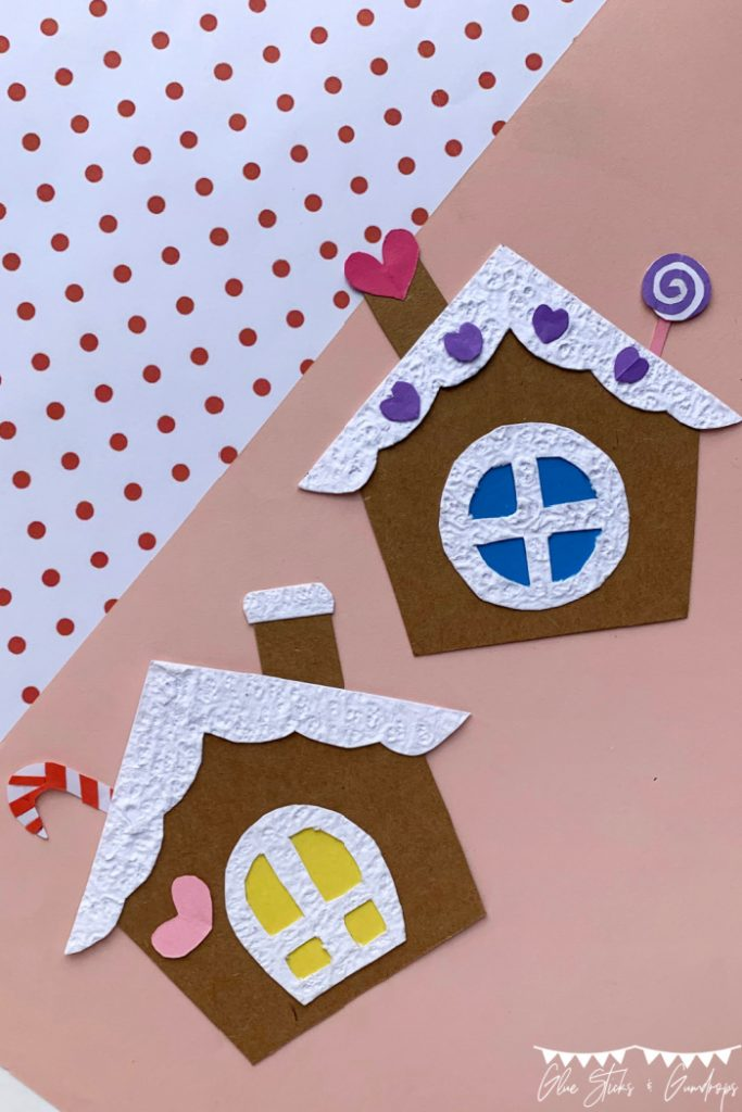 two paper gingerbread houses on light pink background