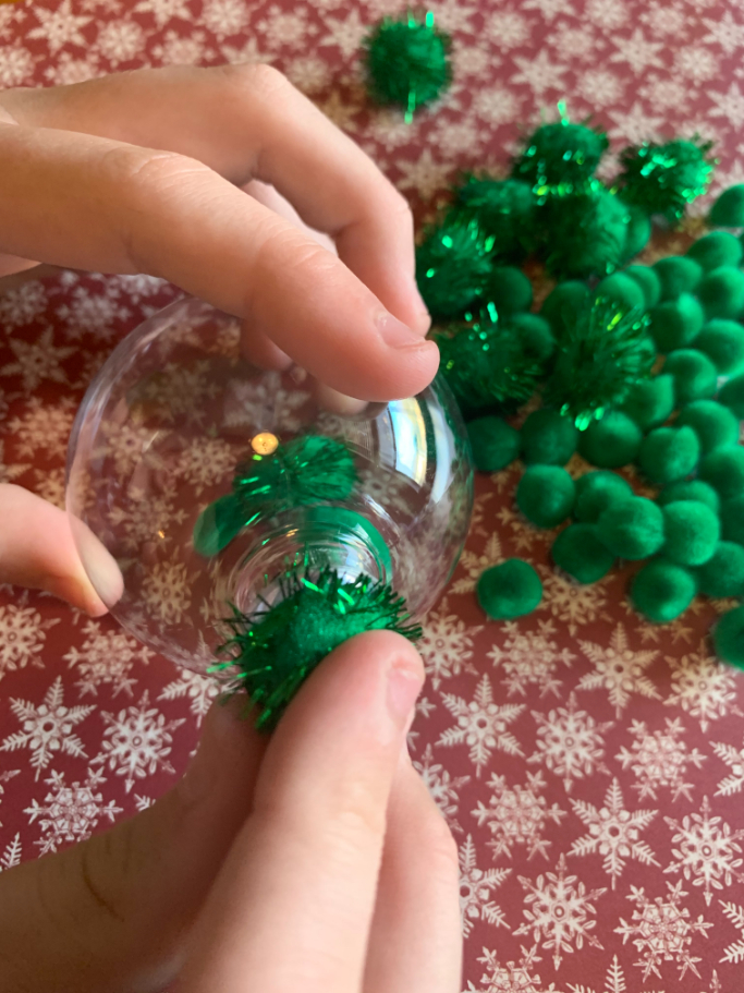 filling the clear ornament with green pom poms