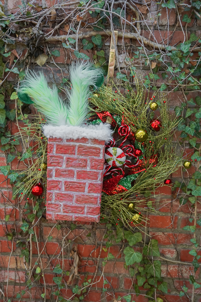grinch in chimney wreath for Christmas