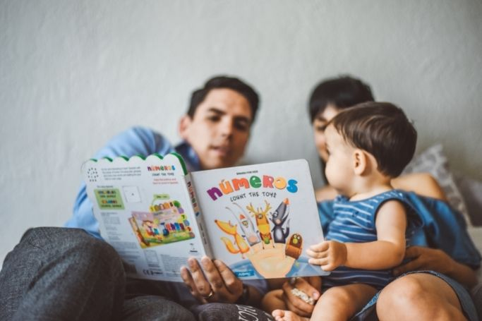dad and mom reading to child