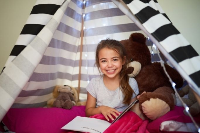 little girl in her reading nook with her teddy bear