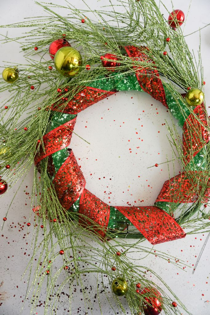 wreath form wrapped in pine garland and red ribbon